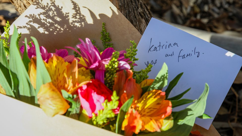 Flowers and a note are left next to a police roadblock where police are investigating the death of seven people in a suspected murder-suicide in Osmington, Western Australia
