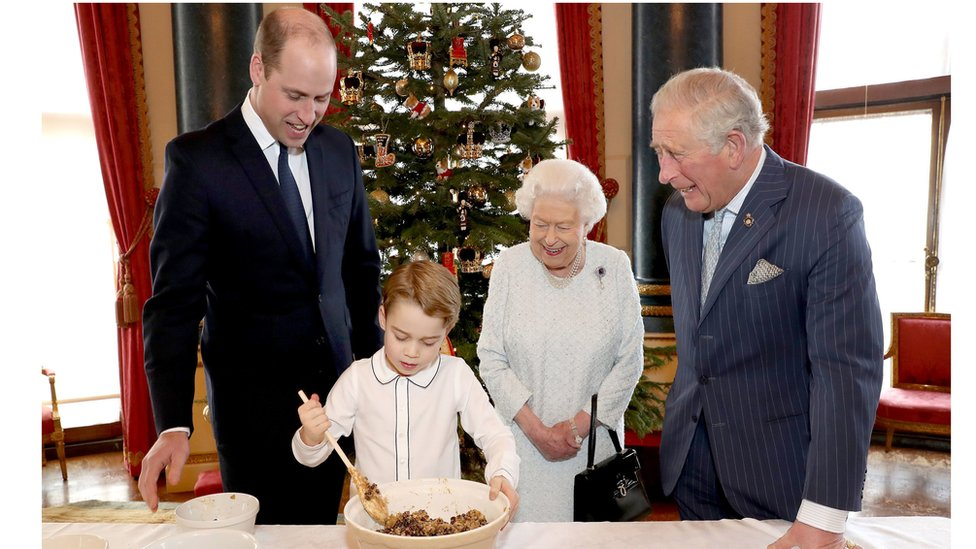 Queen Elizabeth II, the Prince of Wales, the Duke of Cambridge and Prince George preparing special Christmas puddings in the Music Room at Buckingham Palace, London, as part of the launch of the Royal British Legion's Together at Christmas initiative