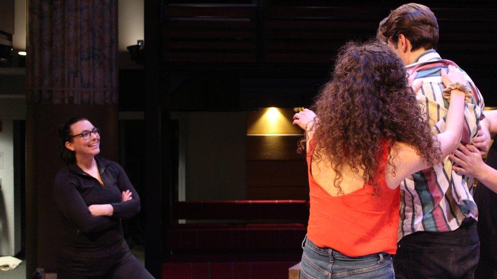 اداکاروں کے ساتھ ریہرسل کرتے ہوئے بائیں جانب چیلسیا پیس کو دیکھا جا سکتا ہے