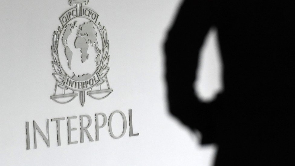 Silhouette next to an Interpol sign