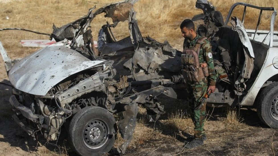 Iraqi militia fighter inspects the remains of a vehicle destroyed in an attack by IS militants that left 10 people dead in Mukaishefah, Iraq (3 May 2020)