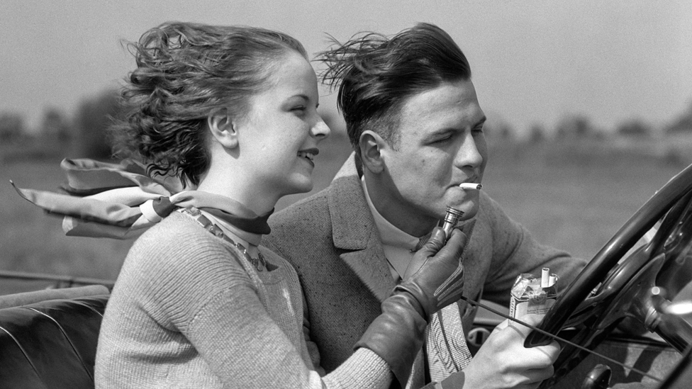 žena pali cigaretu muškarcu