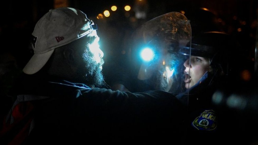 A protester faces an officer in riot gear