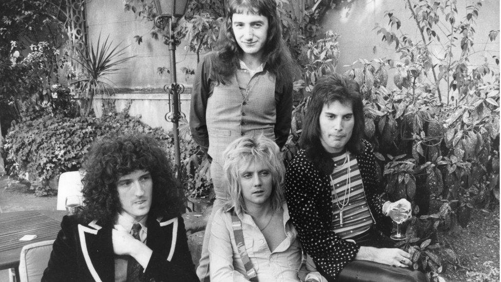 Soldan sağa Brian May, John Deacon (ayakta), Roger Taylor ve Freddie Mercury