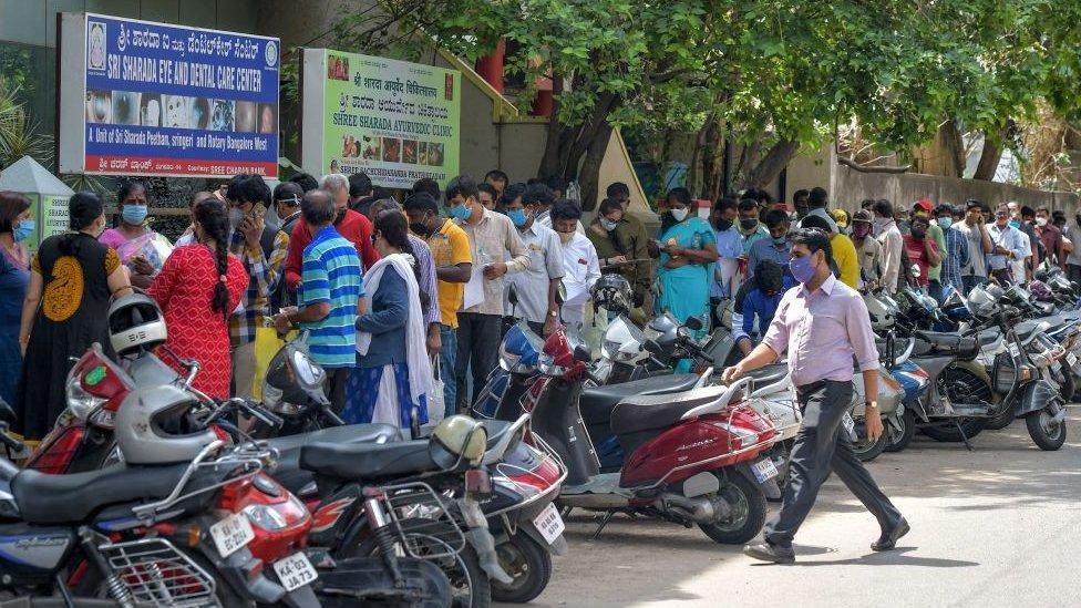 Orang-orang mengantri di luar rumah sakit di Bangalore.