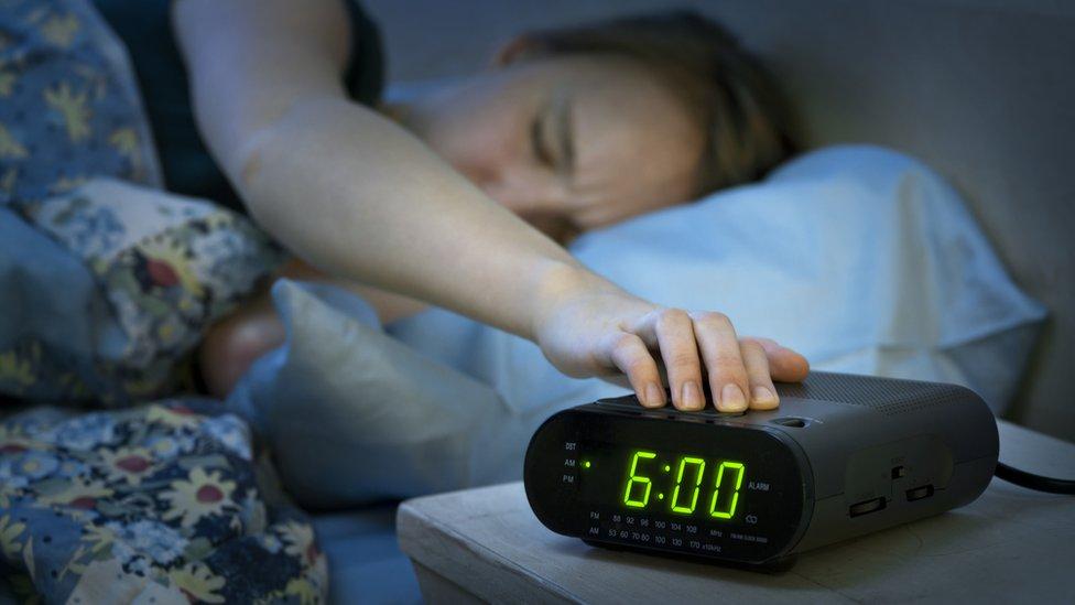 Mujer posponiendo despertador.
