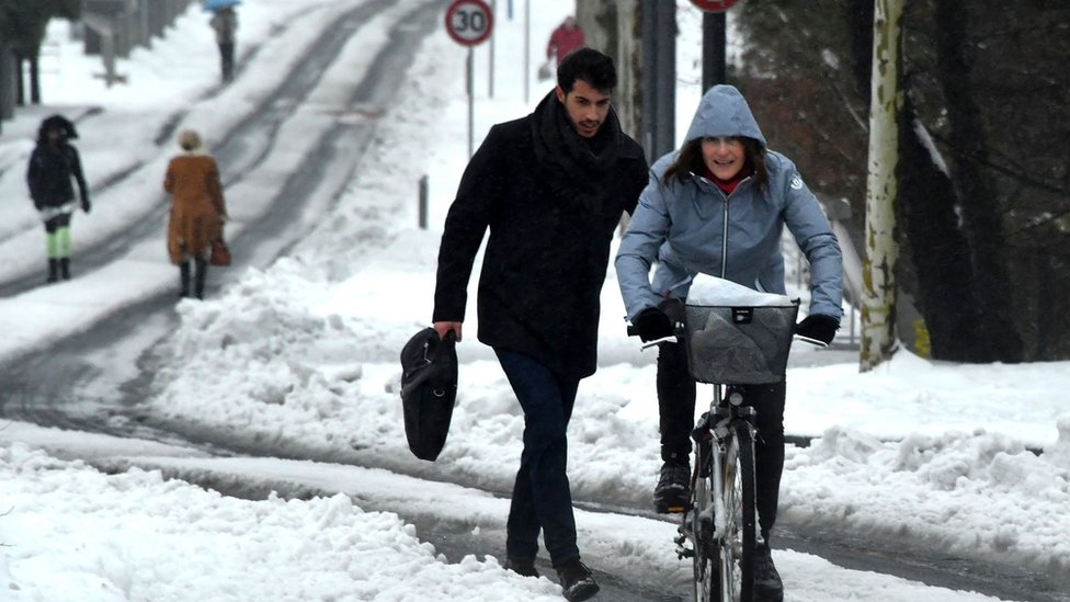 A pedestrian and a cyclist travel along a snow-covered street in Montpellier, southern France, on March 1, 2018