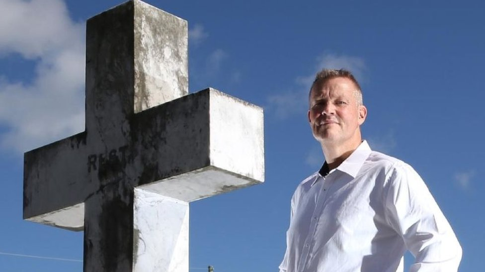 Bill Edgar standing next to a stone cross