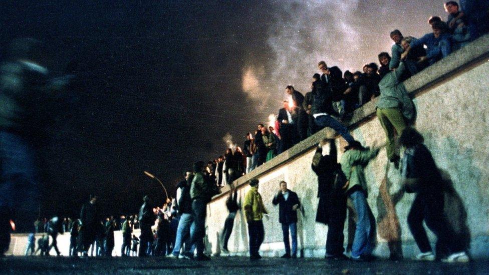 Građani Istočne Nemačke na Berlinskom zidu kod Brandenburške kapije 1989.