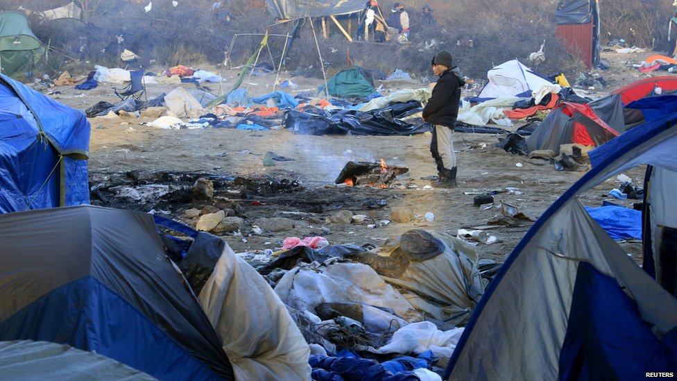"""Migrants warm their hands near a wood fire in a dismantled area of the camp known as the """"Jungle"""""""