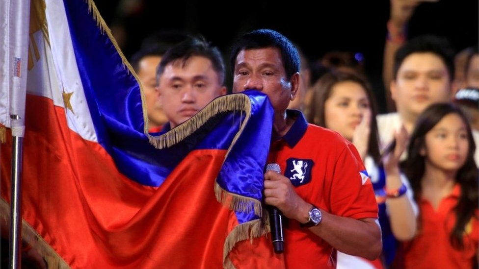 Rodrigo Duterte kisses a Philippines flag in Manila (7 May 2016)