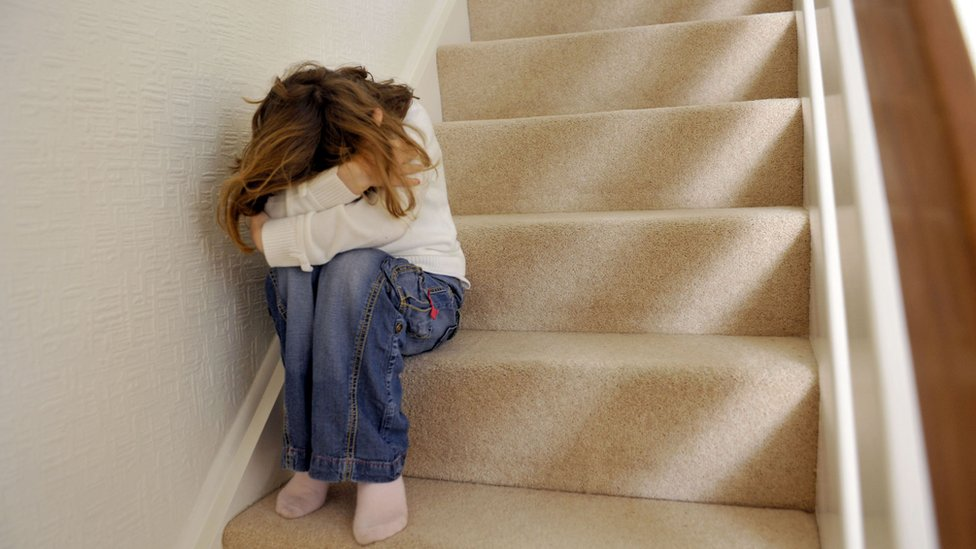 Stock image of child sitting on stairs hiding