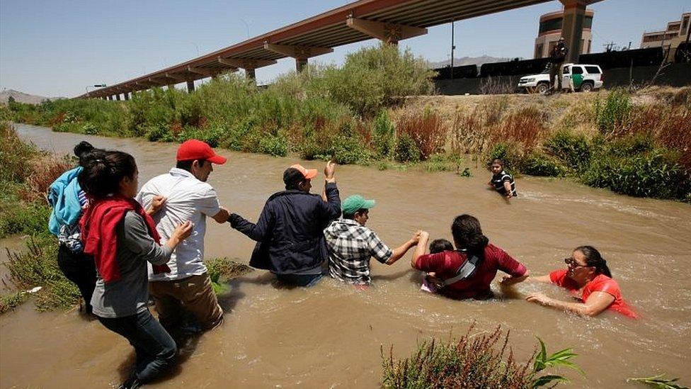 Migrantes cruzando un río fronterizo