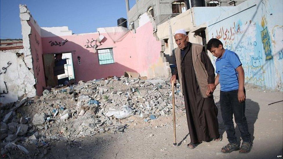 فلسطينيان يسيران بجانب الأنقاض في غزة 2014
