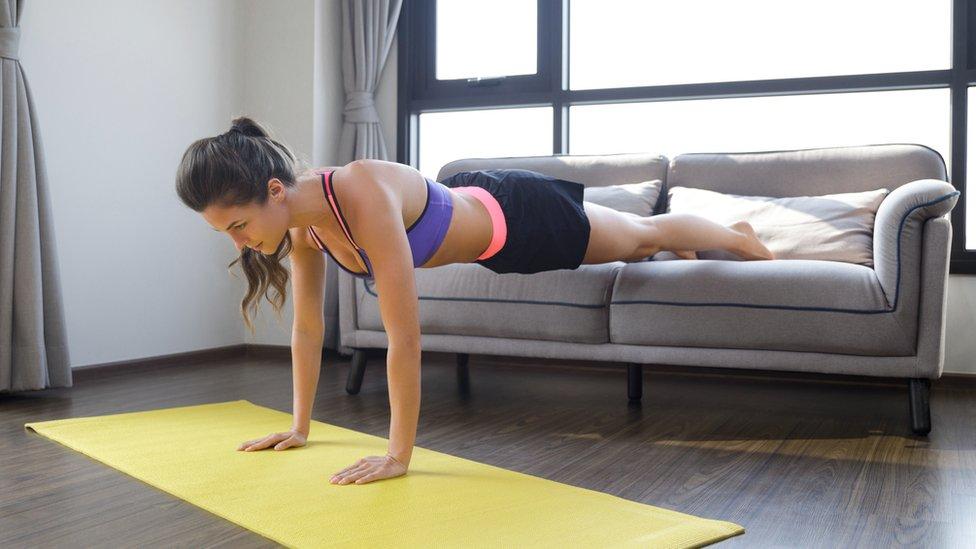 Una mujer haciendo planchas con las piernas apoyadas en un sofá.
