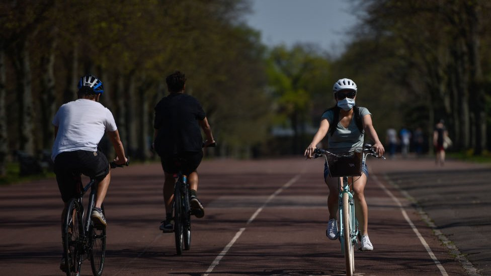 A cyclist wearing a mask is seen in Greenwich Park