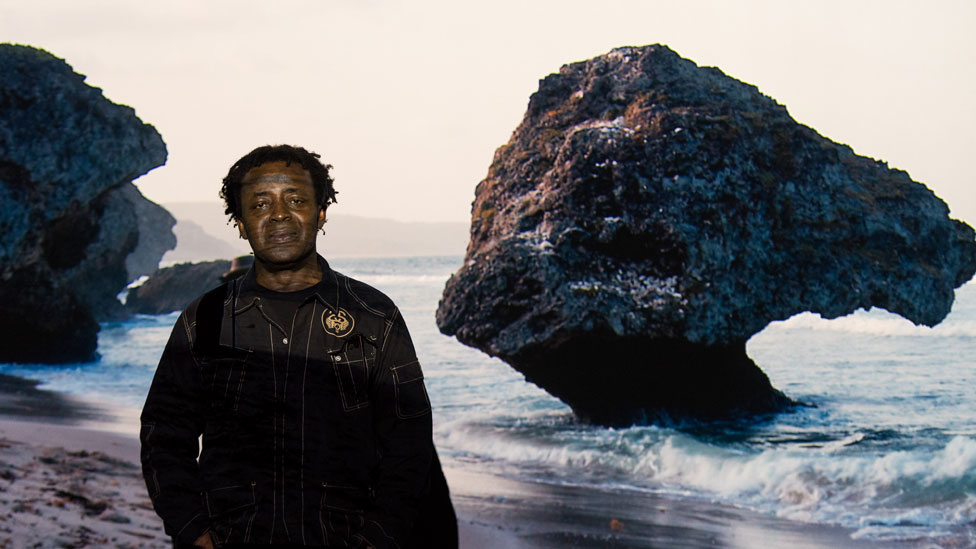 John Akomfrah in front of his installation on show in Cardiff