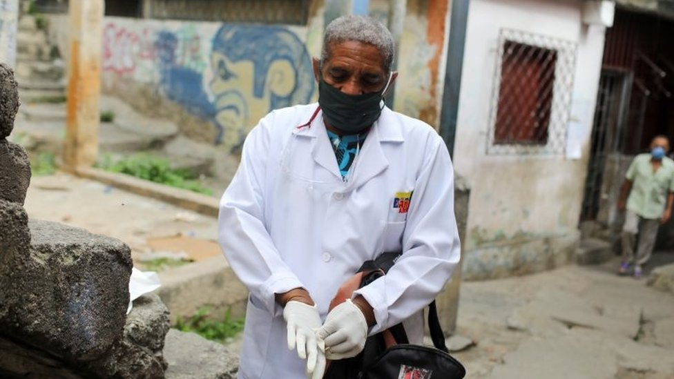 A doctor puts on gloves during a walking round at the low-income neighbourhood of Las Mayas, as cases rise amid the coronavirus disease (COVID-19) outbreak, in Caracas, Venezuela July 14, 2020.