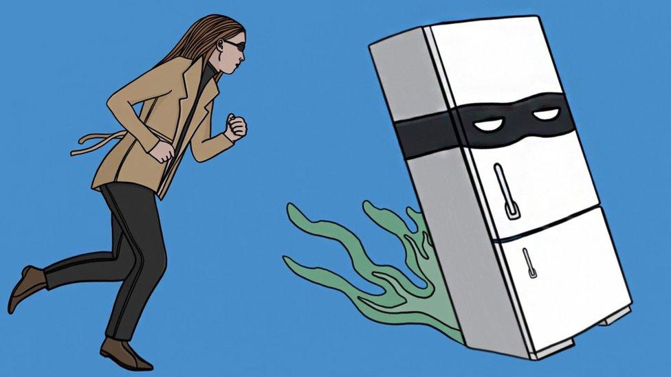 A woman chasing a fridge wearing a villain's face
