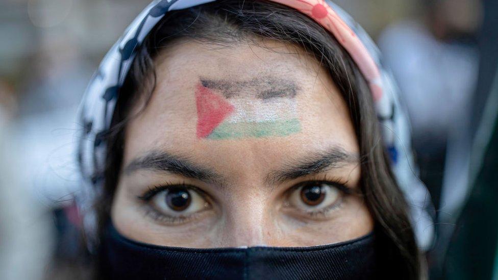 Mujer de origen palestino lleva la bandera de su país en la frente.