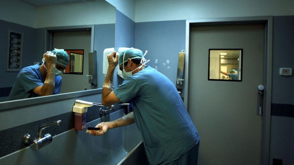 Anggota staf kesehatan sedang mencuci tangan.