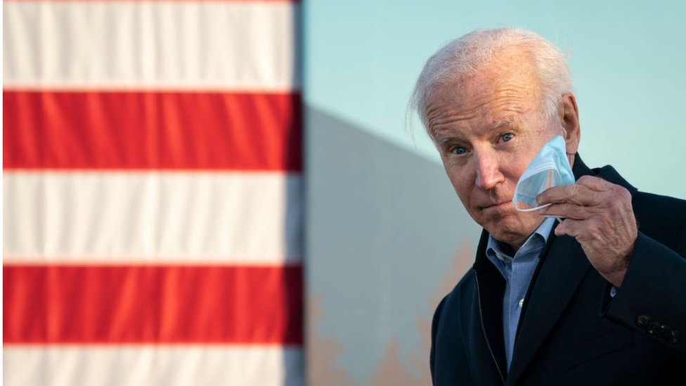 Biden holds his mask in his hand at a rally in Minneapolis