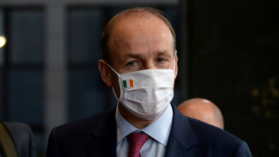 Taoiseach Micheál Martin wearing a face covering with an Irish flag attached