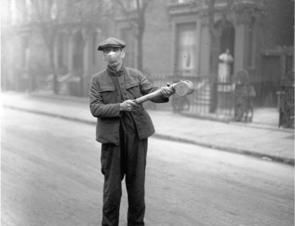 Un hombre rocía espray antigripal en las calles de Londres.