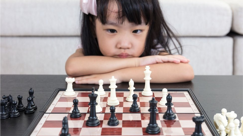 A girl looking serious while staring at a chess board