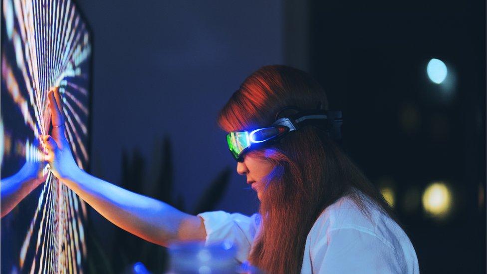 Una mujer tocando una pantalla