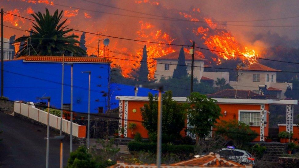 La lava fluye detrás de las casas en Canarias, España.