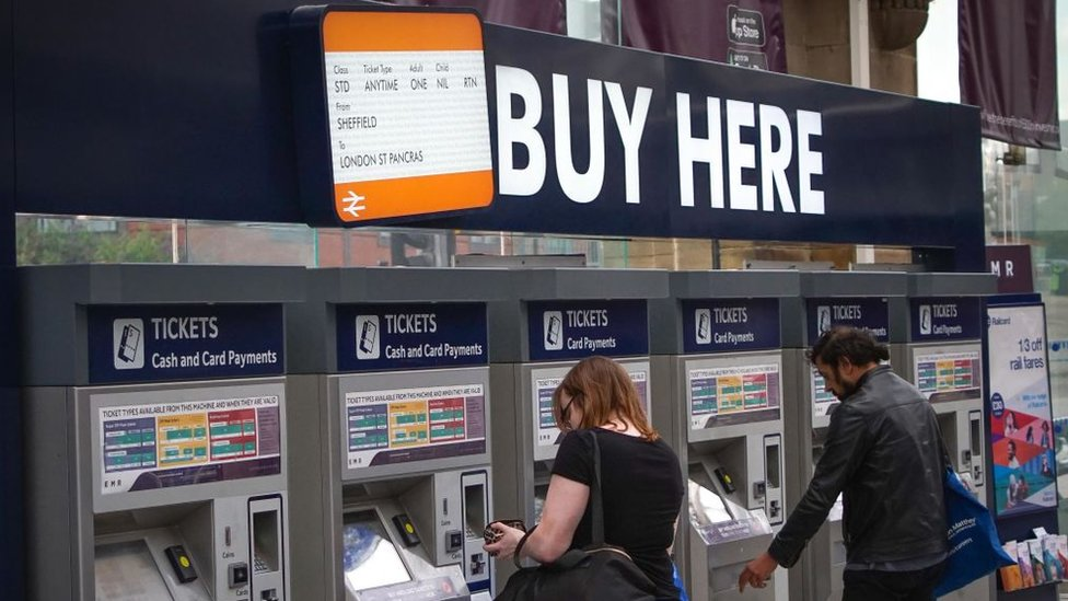People buying train tickets from ticket machines at Sheffield train station