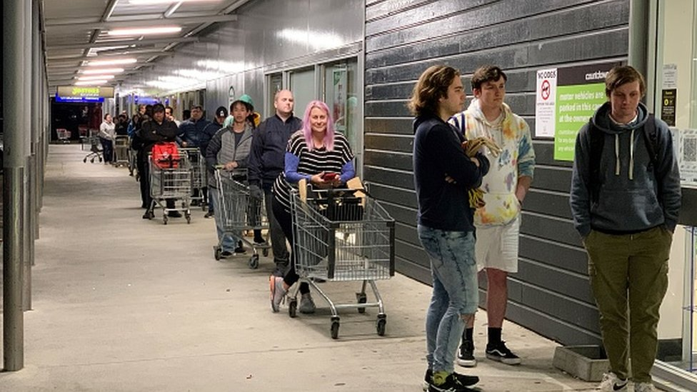 Shoppers wait to enter a supermarket in the suburb of Johnsonville in Wellington