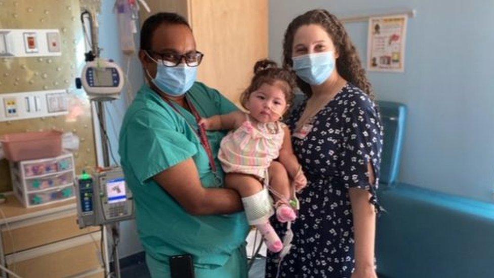 Los médicos Raghav Murthy y Lauren Glass, quienes lideraron el equipo responsable de cuidar a la bebé en el hospital infantil Kravis, junto a la bebé.