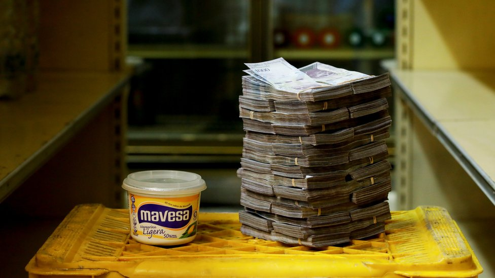 A tub of margarine is pictured next to a stack of 3 million bolivars - equivalent to 46 US cents at a market in Caracas on 16 August