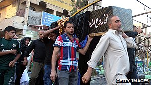 Coffin at the scene of a bombing in Baghdad