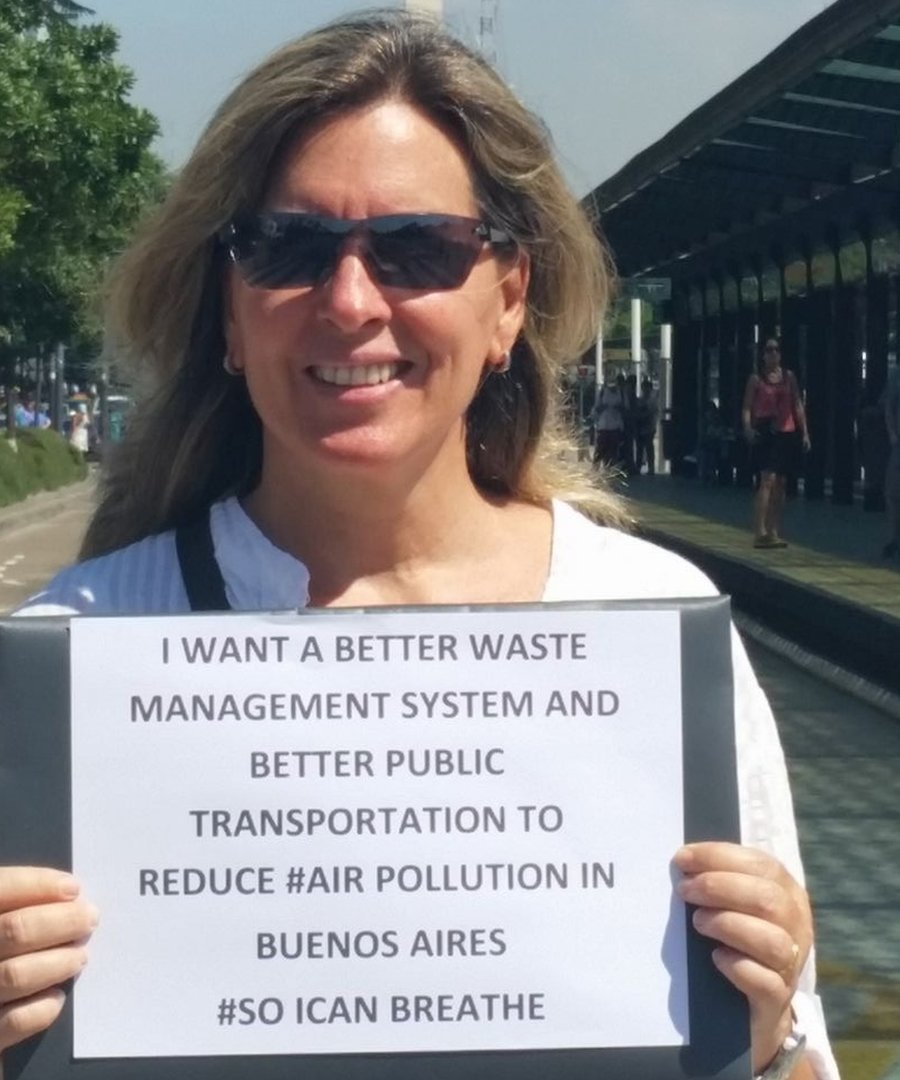 Maria Innes in Buenos Aires holding a sign: I want a better waste management system and better public transportation to reduce #AirPollution in Buenos Aires #SoICanBreathe