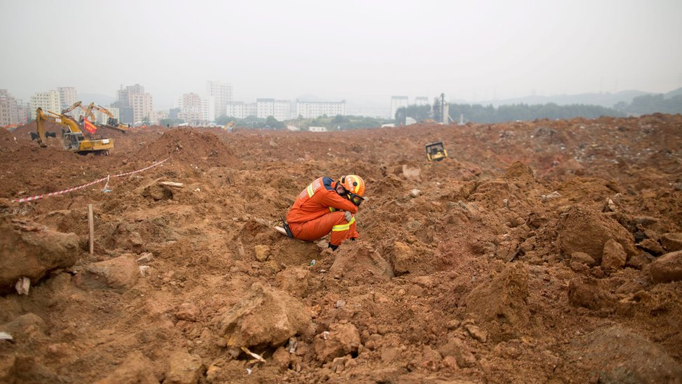 An exhausted rescuer takes a rest as he sits on the mud left behind by the Shenzhen landslide