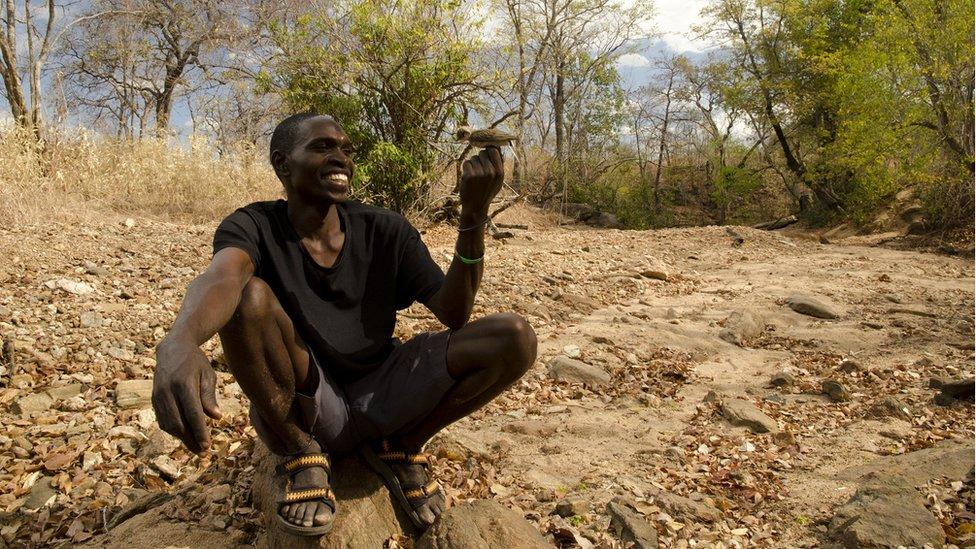 hunter holding honeyguide bird