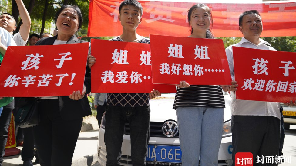 Kang Ying's family hold up placards to greet her