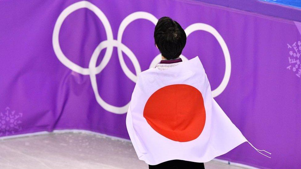 Un atleta japonés de espaldas envuelto en la bandera del país frente a los anillos de los Juegos Olímpicos.