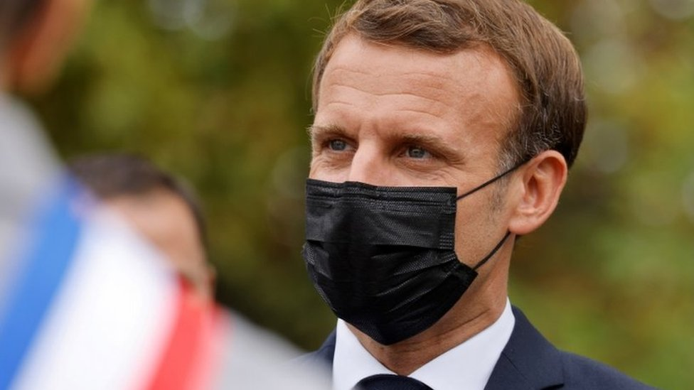 "French President Emmanuel Macron wearing a protective face mask speaks arriving at ""la Maison des habitants"" (MDH) to meet and have lunch with young representatives of the MDH in Les Mureaux, outside Paris, 2 October 2020"