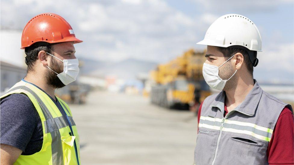 Obreros de construcción con mascarillas