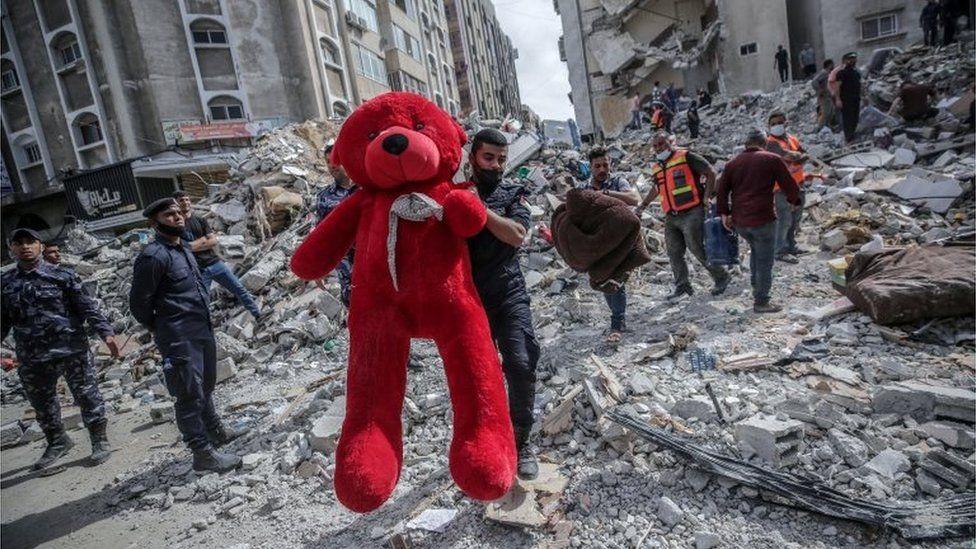 عامل انقاذ في غزة يحمل دمية أخرجت من بين أنقاض المباني المدمرة