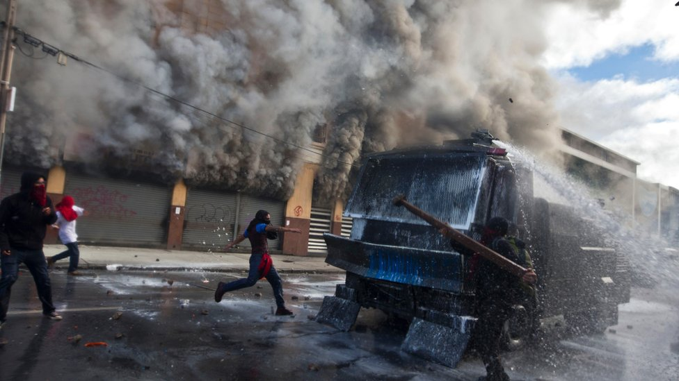 Masked protesters attack a police water canon in front of a burning pharamacy