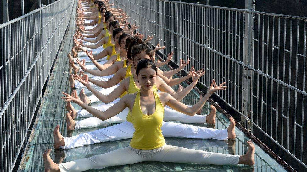 Women practice yoga during a performance on the Brave Man's Bridge glass bridge in Shiniuzhai, Pingjiang county, Hunan province