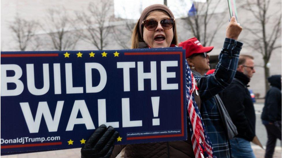 """Una simpatizante de Trump con un cartel que dice """"Construyan el muro"""""""