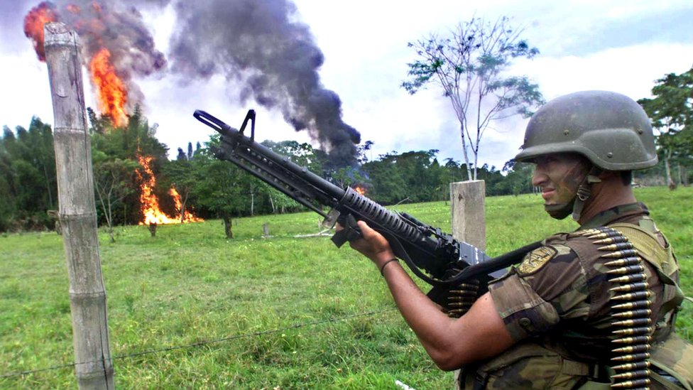 A Colombian Army soldiers stands guard as cocaine paste is destroyed by fire 12 February 2001 in Puerto Asis, Colombia