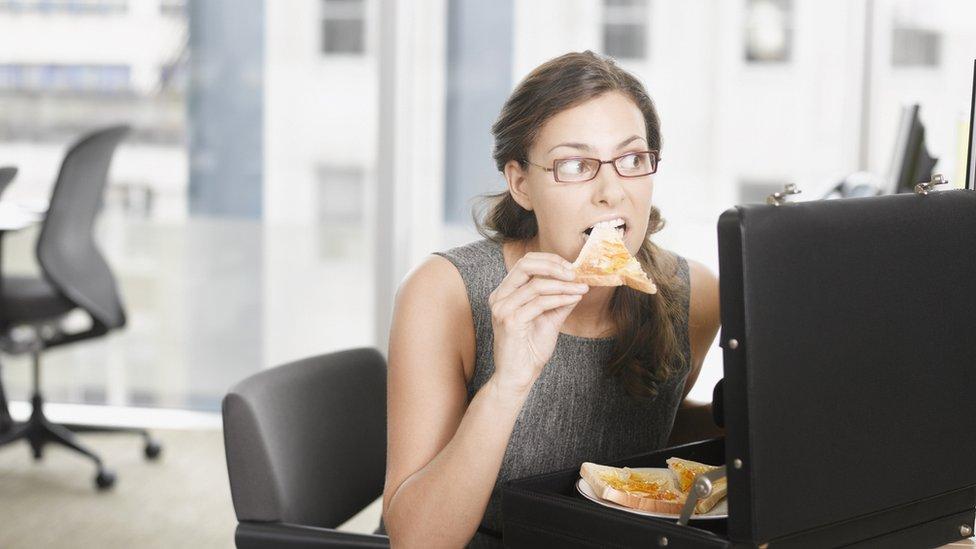 Mujer comiendo en el trabajo.