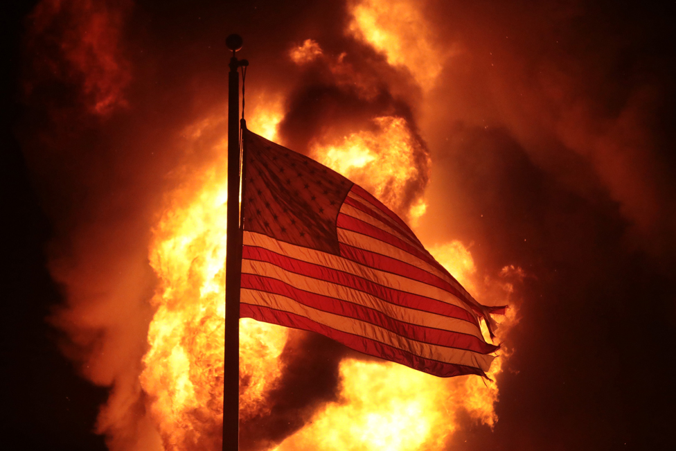 A US flag, with flames in the background